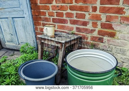 Empty Dishes For Water And Soap Lying On A Stool Against A Brick Wall In Spring-summer Day Outdoors.