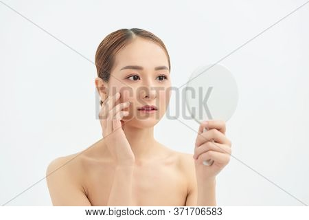 Young Asian Woman With Problem Face Looking At The Mirror  Over White Background.