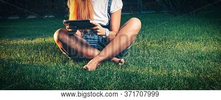 Studente In Park E-learning On Tablet Pc Sitting Cross-legged On The Grass