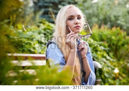Pretty Teenage Girl 14-16 Year Old With Curly Long Blonde Hair And In Glasses In The Green Park In A