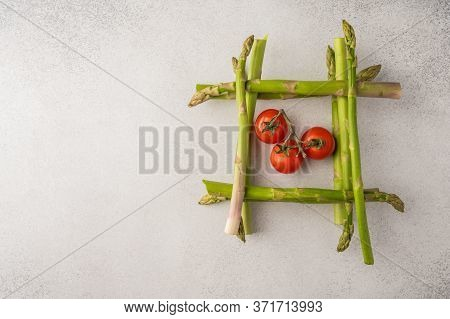Fresh Asparagus Stems In The Shape Of A Well Inside Cherry Tomatoes With Copy Space. Food Concept To