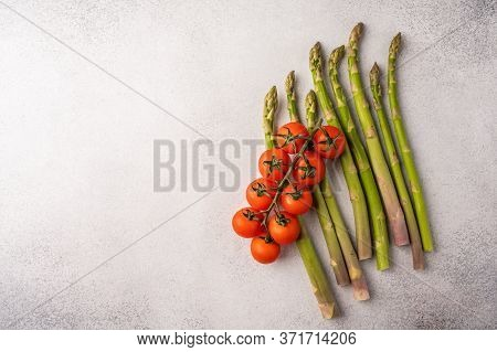 Stems Of Fresh Asparagus And A Branch Of Cherry Tomatoes On A Light Wooden Background Top View With