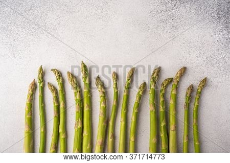 Stems Of Fresh Asparagus Are Lined Up Against A Light Background. Copy Space For Text