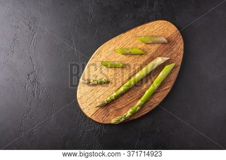 Stems And Pieces Of Asparagus On A Cutting Wooden Board On A Dark Graphite Background. Top View With