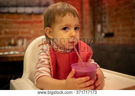 A Little Cute Kid Sits In A Highchair, Holds A Glass Of Juice With His Hands And Drinks From A Straw