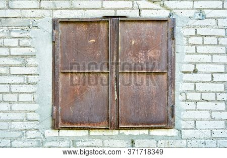 Window Opening For Unloading Goods In Store Closed By Rusty Iron Shutters On White Brick Wall. Shutt