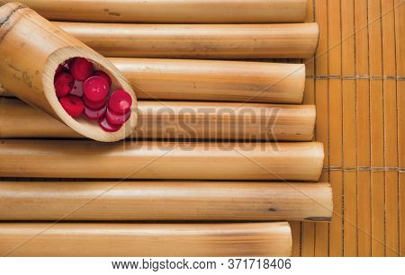 Bamboo Sticks And Bamboo Napkin With Red Coral Beads. Traditional Bamboo Pad With Parts Of Dry Bambo