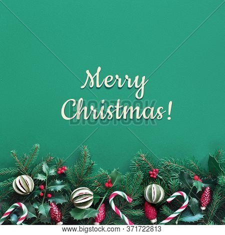 Creative Christmas Flat Lay On Green Paper With Red Decorations. Square Composition, Greeting Text M