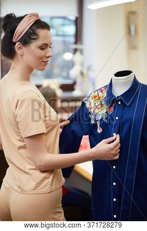 Pretty Young Girl Adjusts Dress On The Mannequin. Blue Dress On A Mannequin. Seamstress In A Sewing