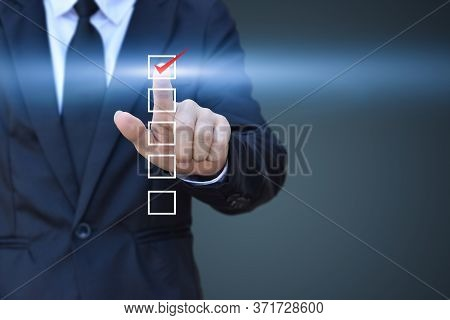 Businessman Touch Checking Mark In A Checkbox On Blue Background. Copy Space