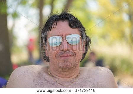Portrait Of A Man Wearing Sunglasses With A Reflection Of A Boat In A Lake