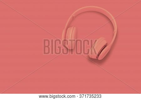A Headphones, Top View Of Headphones On  Orange Color Background. Minimalist Photo Of Earphones With