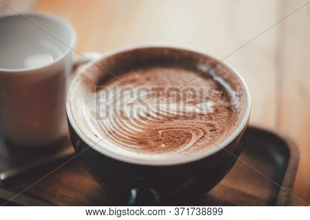 Delicious Hot Chocolate With Froth Art On Top Of Wooden Table In Cafe
