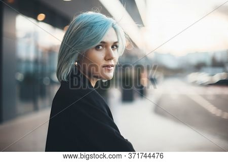 Charming Caucasian Woman With Blue Hair Looking Back At Camera While Cheering Outside In The Street
