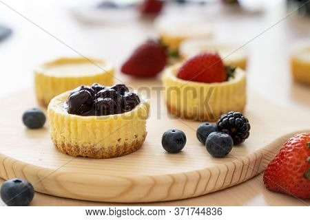 Mini Cheesecake With Blueberry, Blackberry And Strawberry Ready To Be Served On Wooden Table
