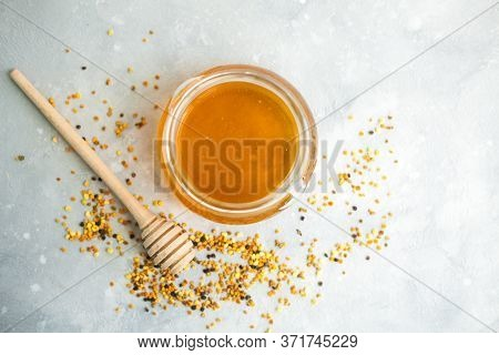 Honey And Honey Spoon On A Light Background. Sweet Honey In A Jar, Pollen Scattered Near The Jar. Pl
