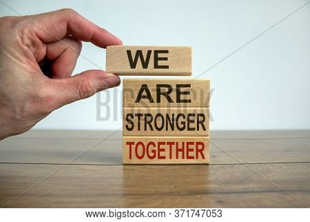 Male Hand Placing A Block With Word 'we' On Top Of A Blocks Tower With Words 'are Stronger Together'