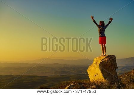 Tourist Woman With Camera Enjoying Sunset Landscape With Arms Raised Up. Mesa Roldan Location In Pro