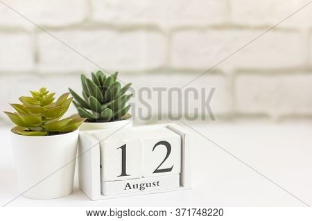 August 12 On A Wooden Calendar Next To The Alarm Clock. Summer Day, Empty Space For Text.calendar Fo