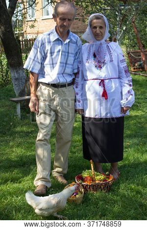 Grandparents On Feast Of The Savior, Funny Senior Couple With Fruit Basket And Chicken