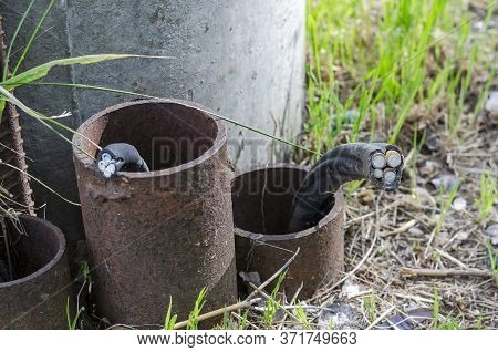 Severed Underground Electric Power Cable. Metal Pipes Stick Out Of The Ground With Bitten Aluminum C