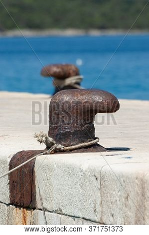 Old And Rusty Mooring Bollard On Concrete Pier With Blue Sea In Background. Sailing, Vacation, Trave