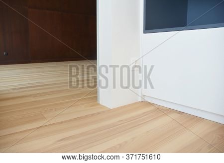 A Close-up On Electrical Socket, Outlet Installed Near The Doorway Close To Wood Laminated Flooring,