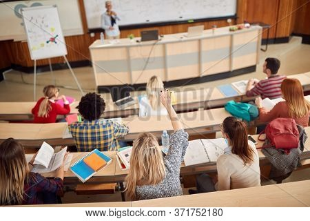 Students on a lecture in amphitheater answering professor's question