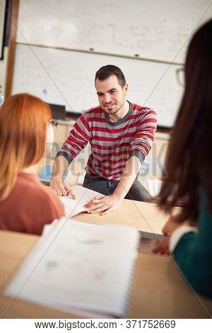 Male colleague helping female classmate in amphitheater