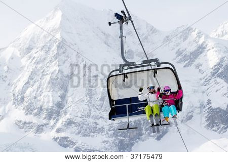 Skiing, winter - happy skiers on ski lift