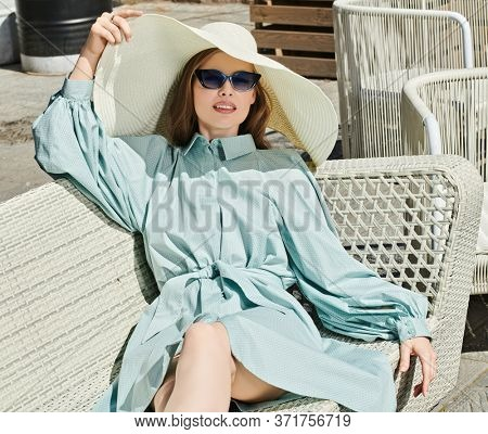 Glamorous young woman in elegant summer dress and a wide brim hat sitting relaxed on a bench on a sunny summer day. Summer vacation. Beauty, fashion.