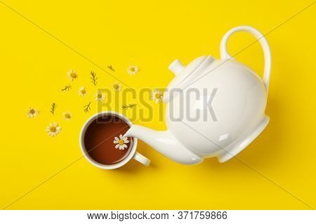 Teapot And Cup Of Chamomile Tea On Yellow Background, Top View