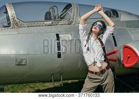 Portrait of a beautiful girl pilot wearing helmet and sunglasses posing next to her fighter jet at the airfield. Military aircraft.