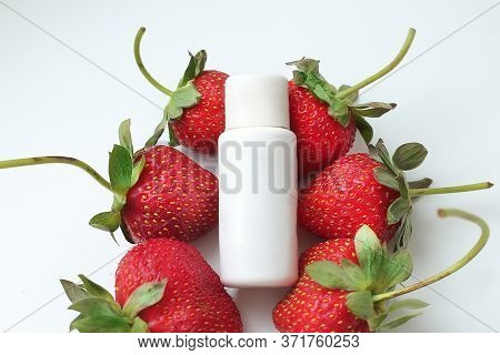 A White Cosmetic Tube Lies On A Strawberry On A White Background. Top View  Strawberry Cosmetics Lie