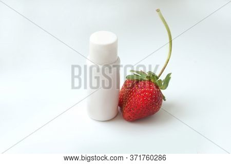 White Cosmetic Tube With Strawberry On White Background. Strawberry Gel With Ripe Fruits Nearby. Iso