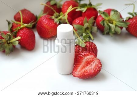 White Free Cosmetic Tube With Strawberry On Strawberry  Background. Strawberry Gel With Ripe Fruits