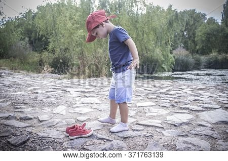 Little Boy Feel His Feet Wet After Walking Into The Brook. Discovering Nature For Children Concept