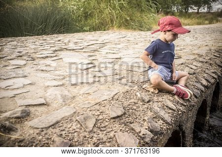 Little Boy Sitting Over Bridge Observing How The Water Flows. Discovering Nature For Children Concep