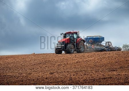A Modern Tractor Plows The Land In An Agricultural Field