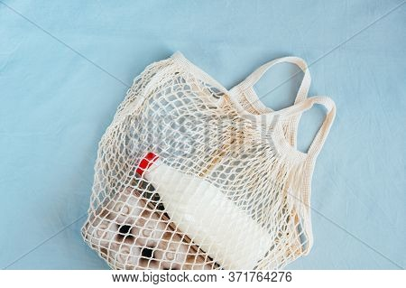 Reusable Net Bag Or Mesh Shopper With Essential Goods - Milk And Eggs , On Blue Tablecloth Backgroun