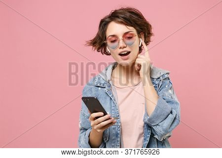 Pretty Young Brunette Woman In Casual Denim Jacket, Eyeglasses Posing Isolated On Pastel Pink Backgr