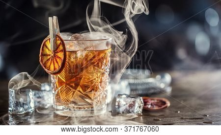 Smoked Old Fashioned Rum Cocktail With Cubes Of Ice Around On A Dark Background.