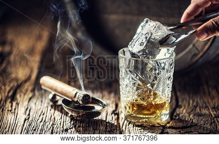 Ice Cube Being Put Into An Ornamental Cup Of Whisky Placed On A Old Fashioned Wood And Burning Cigar