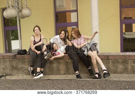 A Group Of Four Fashionable Teenager Friend Girls Sitting, Laughing, Smiling And Hugging On The Stre