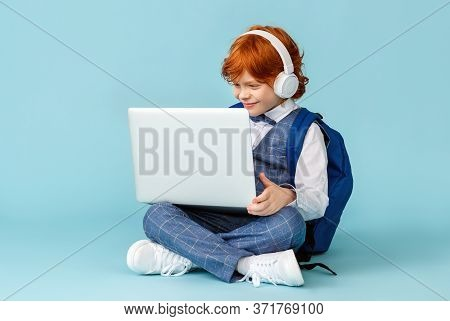 Positive Little Red-haired Schoolboy In Headphones Smiling And  Learn Remotely On Modern Laptop Whil