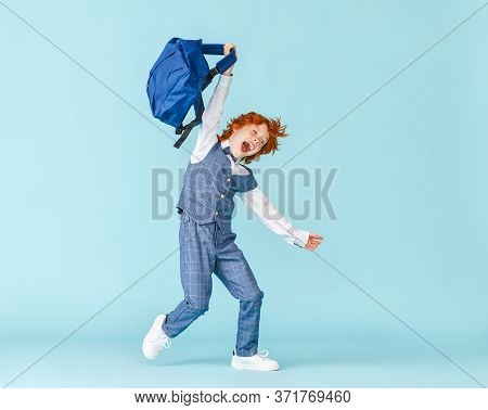 Full Body Delighted Boy In School Uniform Screaming And Leaping Up And Runing Around Waving A Backpa