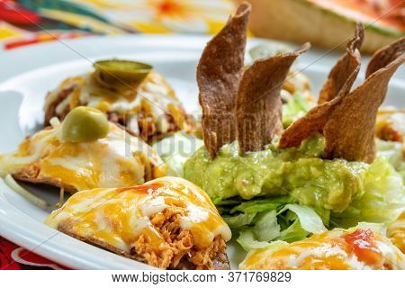 Macro Close Up Of Appetizing Mexican Chicken Nachos. Melted Cheese And Guacamole Dip With Crispy Fri