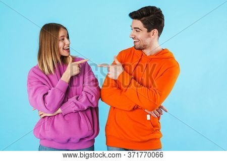 Image of happy loving couple isolated over blue wall background pointing at each other.