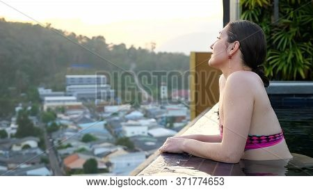 Happy Girl Enjoys Pictorial Landscape Standing In Hotel Swimming Pool In Summer Evening Closeup Copy