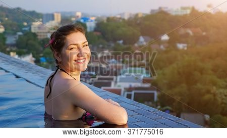 Lady In Swimsuit Looks And Smiles Relaxing In Hotel Outdoor Swimming Pool Against Blurry Forestry Hi
